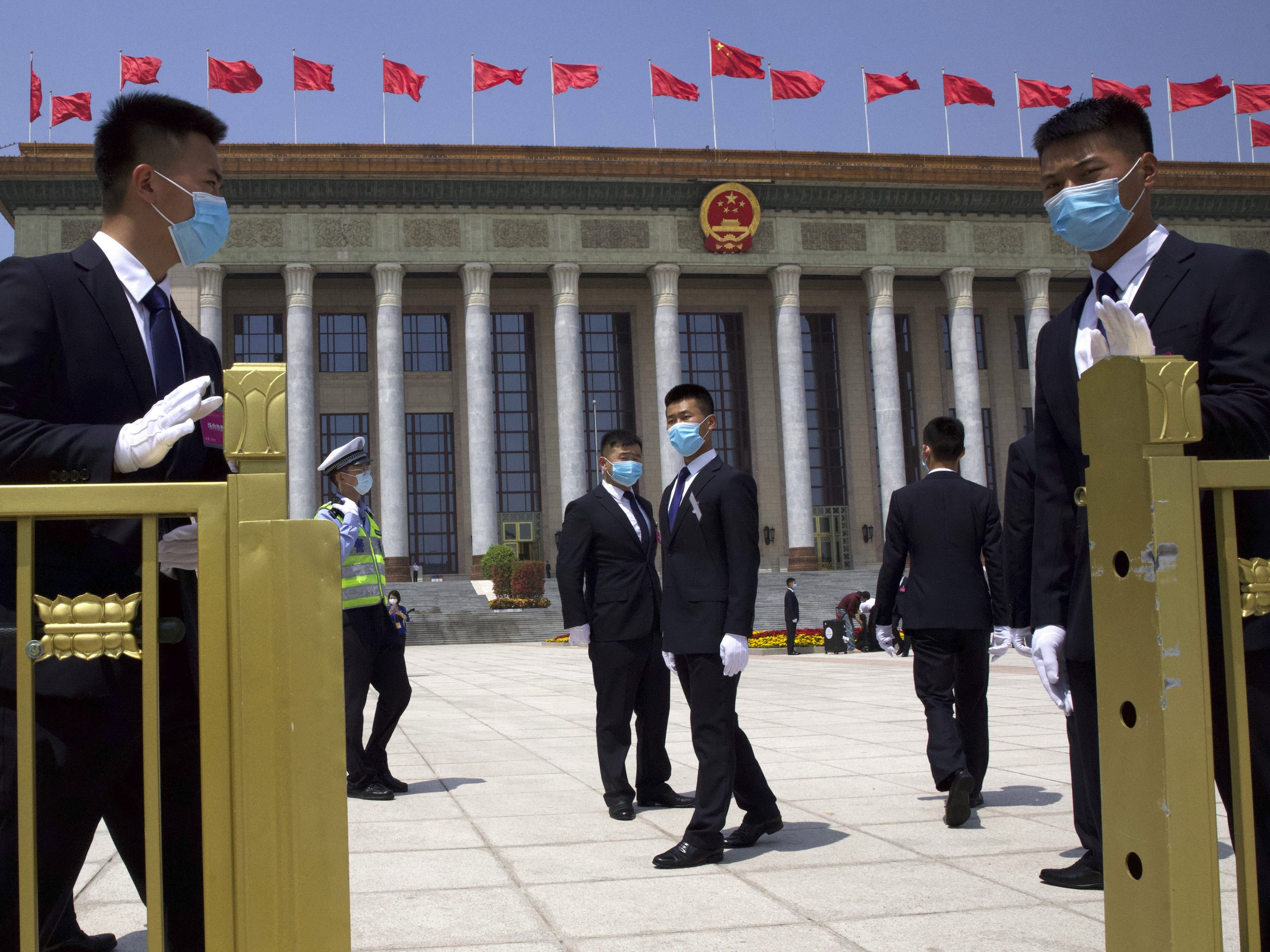 Chinese security officials wear face masks to protect against the new coronavirus as they stand guard outside the Great Hall of the People after the opening session of China's National People's Congress (NPC) in Beijing.