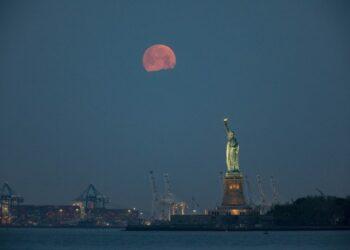 Bulan terlihat di atas Patung Liberty di New York, Amerika Serikat, pada 26 Mei 2021. (Xinhua/Wang Ying)