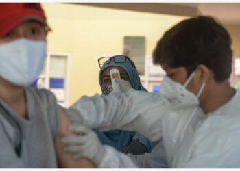 Seorang wanita menjalani pemeriksaan suhu tubuh sebelum menerima satu dosis vaksin COVID-19 di Tangerang Selatan pada 14 Juni 2021. (Xinhua)