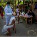 Seorang pekerja kesehatan India dengan berpakaian pelindung lengkap melakukan tes usap (swab) Covid-19