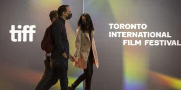 Orang-orang yang mengenakan masker berjalan melewati dinding dengan logo Festival Film Internasional Toronto (Toronto International Film Festival/TIFF) di TIFF Bell Lightbox, markas ajang TIFF 2021, di Toronto, Kanada, pada 9 September 2021. (Xinhua/Zou Zheng)