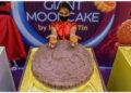 Seorang staf menunjukkan sejumlah kue bulan di atas kue bulan raksasa yang dipajang dalam perayaan Festival Pertengahan Musim Gugur di kawasan Pecinan di Manila, Filipina, pada 17 September 2021. (Xinhua/Rouelle Umali)